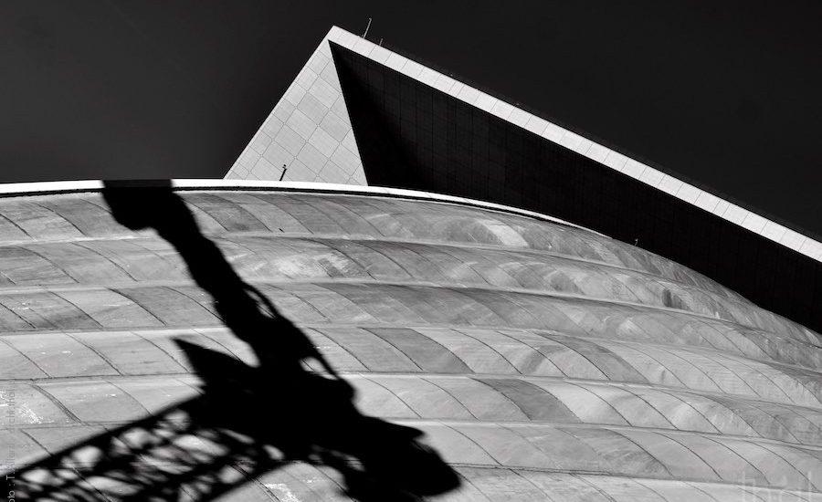 Ombre d'une grue sur le toit du CNIT devant la grande Arche
