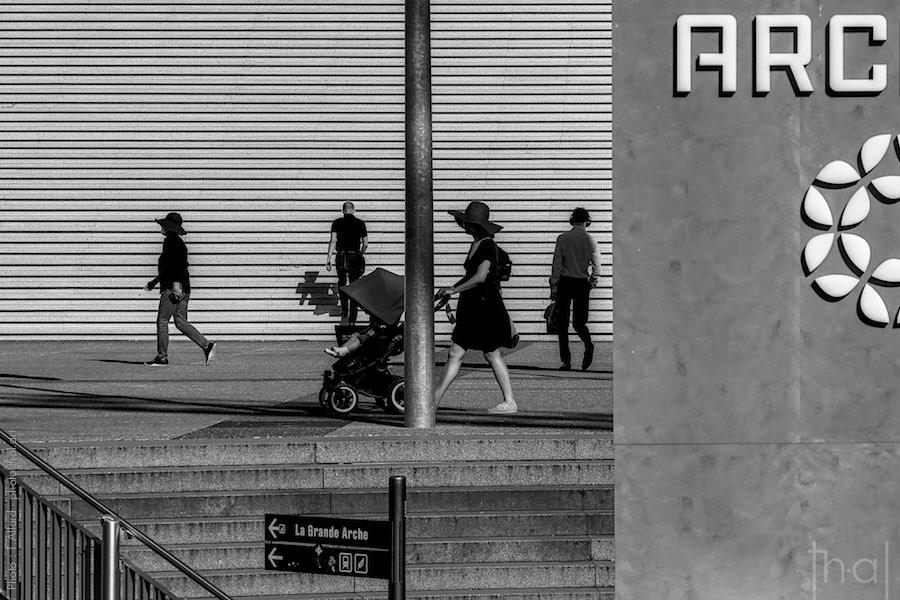 Passants devant les marches de la Grande Arche